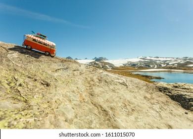 SOGNEFJELLET, NORWAY - JULY 7, 2018: Miniature scale model hippy VW van in norwegian mountains, tourist route Sognefjellet, the highest mountain road in Northern Europe
