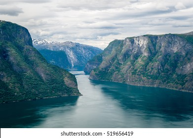Sognefjord rocky mountains and calm water landscape at typical norwegian cloudy summer day. Flam, Norway.