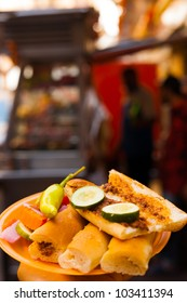 Sogo, a traditional Egyptian street food sandwich is served from food carts with pickles and a sausage meat on a plate