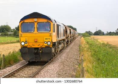 SOHAM, CAMBRIDGESHIRE, UK - AUGUST 19, 2012: GBRf Class 66 No. 66711 works the 6T65 Colchester to Whitemoor engineer's train, consisting of a train of autoballasters, seen here passing through Soham.