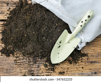 Soil with bag for planting on wood background and agriculture tool