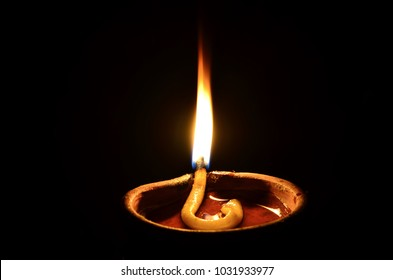 soil or clay lamp radiating light in dark. concept of removing darkness with a flame. this types of lamps are common in india and nepal, especially in diwali. lamp has oil and cotton wick. hindu uses