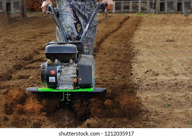 Soil cultivation. The cultivator loosens the ground. The farmer works with a motor-block. Agriculture.