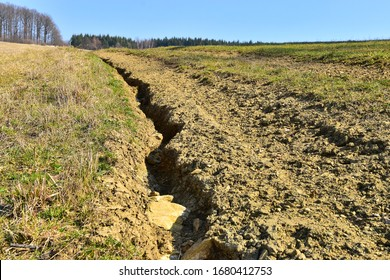 Soil erosion erosive groove in field road, damaged earth in farmer land.