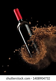 Soil explosion over a red wine bottle