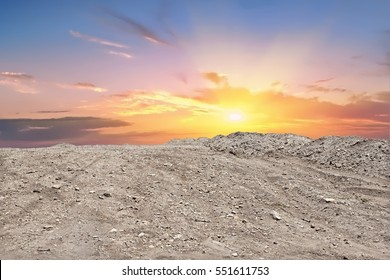 Soil mountain ground and the sunset or sundown  with a yellow sun and red with blue sky clouds. there are rocks  on the ground