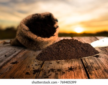 Soil for planting with bag over sunset background