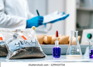 Soil Samples Testing Laboratory. Close up image of female scientist wearing white coat taking notes in laboratory.