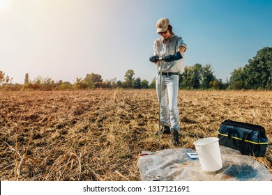 Soil Sampling. Female agronomist taking sample with soil probe sampler. Environmental protection, organic soil certification, research