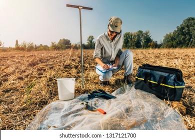 Bodentest. Frauenagronomist, der Notizen auf dem Feld nimmt. Umweltschutz, ökologische Bodenzertifizierung, Forschung