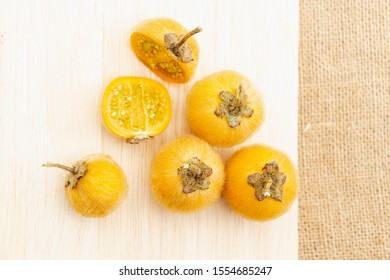 Solanum stramonifolium or coconilla fruit. Food ingredient and herb for healthy on chopping wood and sackcloth background.