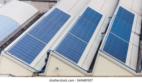 Solar batteries at roof of building. Sustainable energy usage.