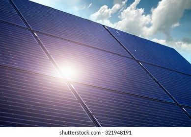 Solar battery panel against blue sky with sun reflection