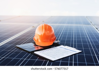 Solar cell contractor document with orange engineering team helmet on solar cells panels. Renewable energy and ecology concept
