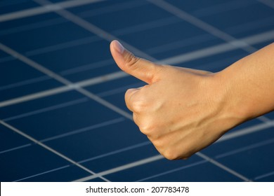 Solar cell panel on roof producing electricity with thumb up