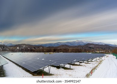 Solar cell panel and village in rural area with mountain landscape background