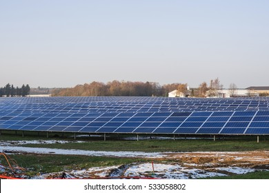 Solar cell park in the winter with snow and blue sky and an industrial building in the background