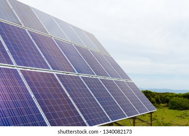 Solar cell photovoltaic panels at energy production plant with blue cloudy sky in the background. Solar renewable energy concept