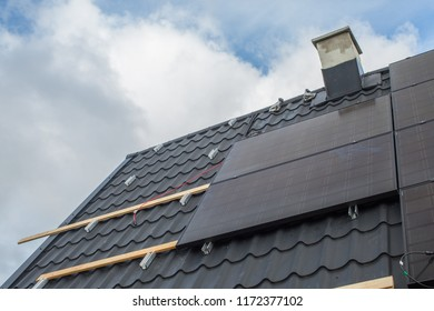 Solar cells being installed on a roof during a summer afternoon.