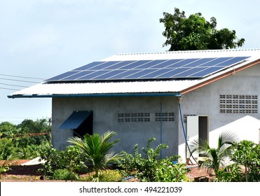 Solar cells for electricity generator on farmer's house roof in rural area of Thailand with clear blue sky background.