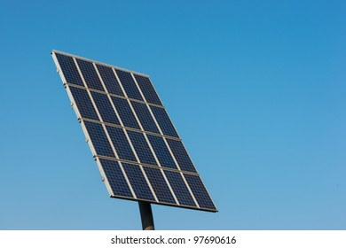 Solar cells generating electricity against a blue sky