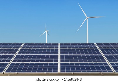 Solar cells or photovoltaic cells with wind turbines generating electricity alternative renewable clean energy in hybrid power plant systems station under blue sky