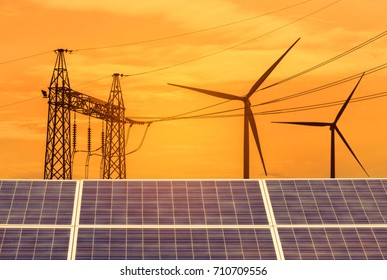 solar cells and wind turbines generating electricity with high voltage electrical power pylon in power station alternative renewable energy from the natural on sunset.