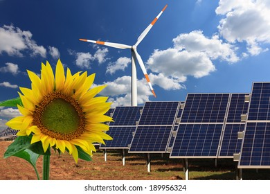 solar collector, windmill and sunflower - blue sky with some clouds