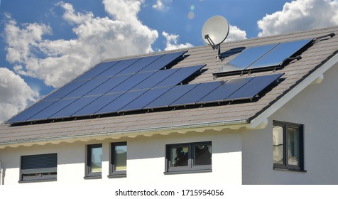 Solar Collectors and Aerial Antenna and on grey tiled Roof of a new built Low Energy House