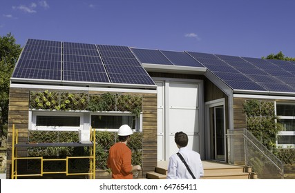 Solar construction workers looking at the roof.  Plants are from a gray water recovery system.