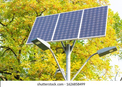 Solar device with street lamp on background of blue sky. Street light powered by solar panel with battery included. Alternative energy from the sun. Copy space