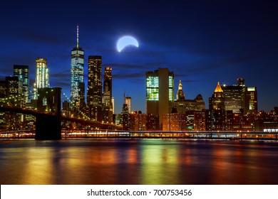 Solar eclipse, New York NY New York City's Brooklyn Bridge and Manhattan skyline illuminated at night