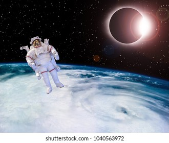 Solar eclipse seen above the earth. Astrounaut is near in space. The elements of this image furnished by NASA.