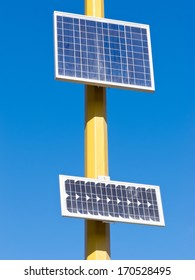 Solar electric panels mounted on yellow pole providing off-grid power in full sun against blue sky