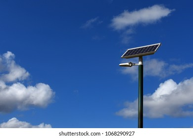 Solar electricity panel on a pole with a blue sky background