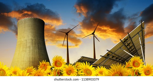 Solar energy panels with wind turbines and cooling tower of nuclear power plant at sunset.