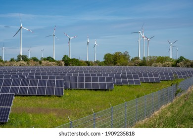 Solar energy panels with wind turbines in the back seen in Germany