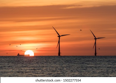 Solar energy and wind power. Climate change and global warming. Offshore windfarm turbines silhouetted by the rising sun with industry in the form of a barge crossing the horizon and nature in birds.