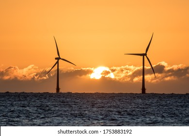 Solar energy and wind power. Sustainable resources. Beautiful sky sunrise behind silouette of wind turbines on soft sea horizon. Clean renewable energy with natural orange sun skyscape.