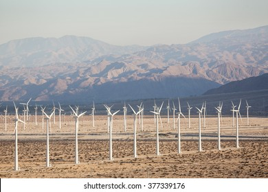 Solar Energy Windmills and Solar Panels in California Mountains in the background. Sunlight, solar panels and wind turbines. Environmental conservation and alternative power generation methods.