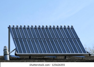 Solar glass tube hot water panel array mounted on a tiled roof against a blue sky