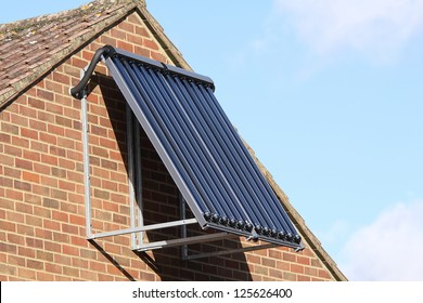 Solar glass tube hot water panel array mounted on a house brick wall against a blue sky