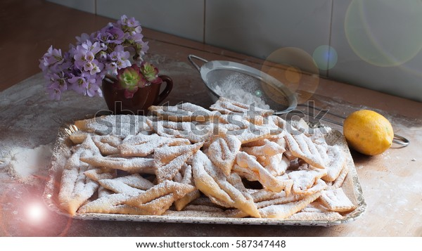 Solar glint on the composition of traditional Italian pastries period of carnivals, sprinkled with powdered sugar and flowers on the wooden table