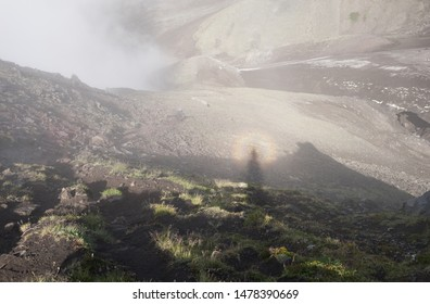 Solar glory and Spectre of the Brocken in misty magical morning in Avacha base camp. Kamchatka Peninsula, Russian far east.  Weather and clouds creating mystical veil of fog in volcanic landscape.