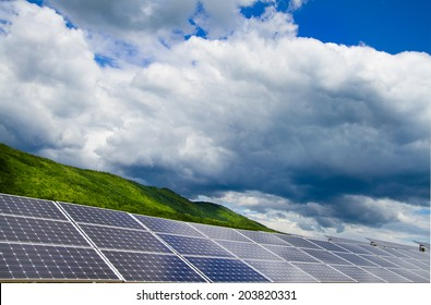 Solar modules row on the background of the green forest and cloudy sky