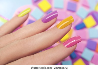 Solar nails are covered with multi-colored with colored lacquer on the female hand.