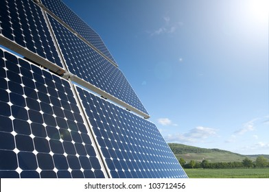 Solar Panel Against Blue Sky With Green Landscape