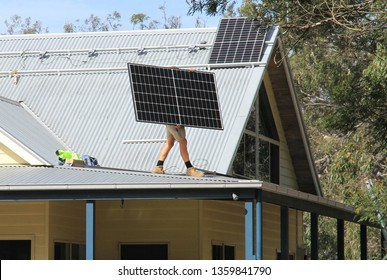 A solar panel being carried onto the roof of a house in Australia