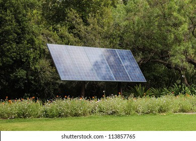 Solar panel in front of trees generating green energy