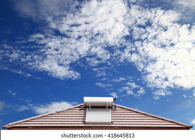 Solar panel for hot water system on roof on blue sky background